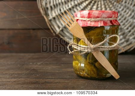 Jar of canned cucumbers on wooden background