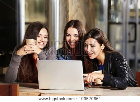 Best friends with laptop together sitting at cafes terrace