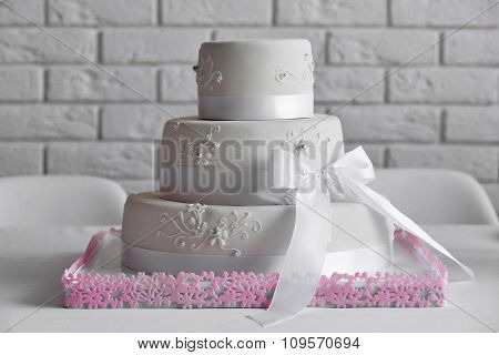 Wedding layered cake on white wall background