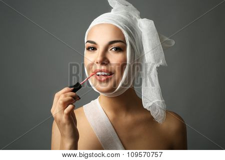 Young emotional woman with a gauze bandage on her head, holding lip gloss, on grey background