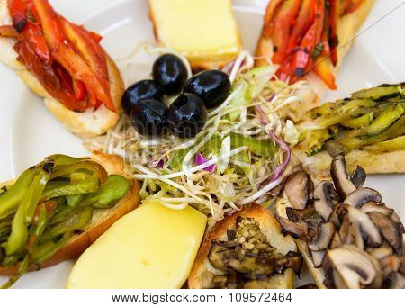 Vegetarian plate with cheese, peppers, olives and mushrooms