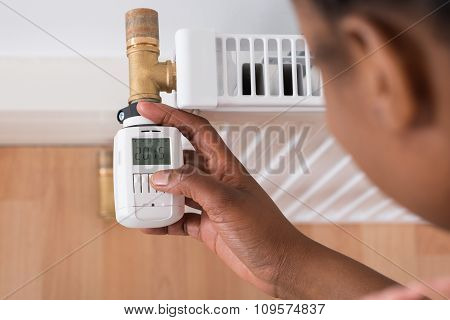 Woman Adjusting Temperature On Thermostat