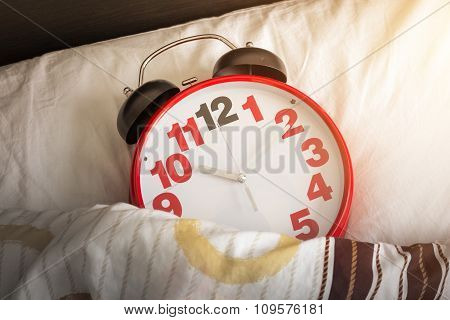 Red Alarm Clock On The Bed With Sunlight
