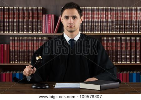 Portrait Of Confident Judge Hitting Mallet At Desk