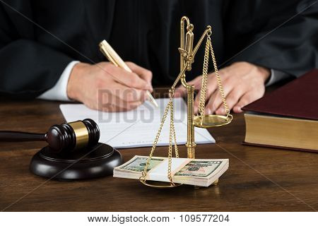 Judge Writing On Document With Banknotes In Weight Scale