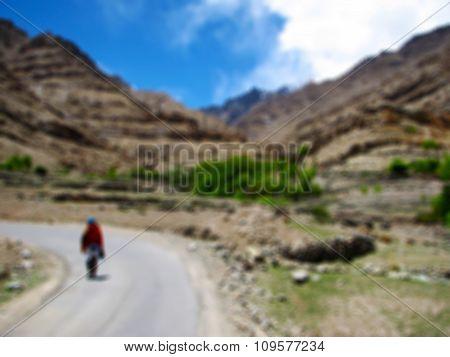 Solo Traveler Walking on Himalayan Mountain Road (blurred background)