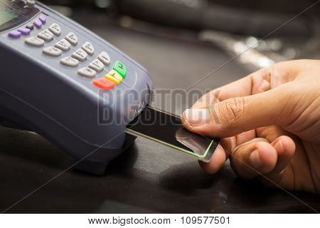 Close Up Of Hand With Credit Card Swipe Through Terminal For Sale In Store : Selective Focus