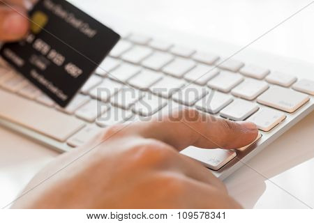 Hand Holding A Credit Card And Typing. On-line Shopping On The Internet
