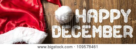 Happy December written on wooden with Santa Hat