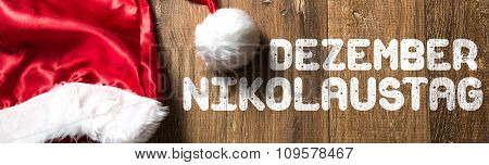 Saint Nicholas Day (in German) written on wooden with Santa Hat