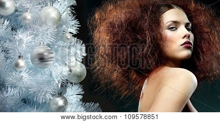 beauty portrait of young caucasian woman face skin makeup hair style lips looking at camera head and shoulders black background fashion christmas tree new year