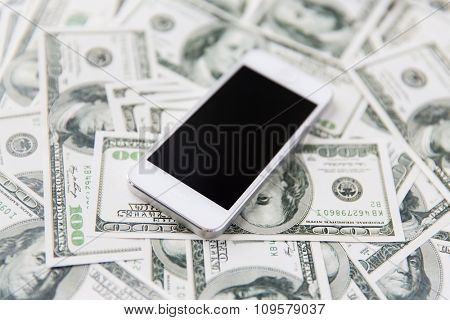 business, finance, technology and e-commerce concept - close up of smartphone with black blank screen and dollar money