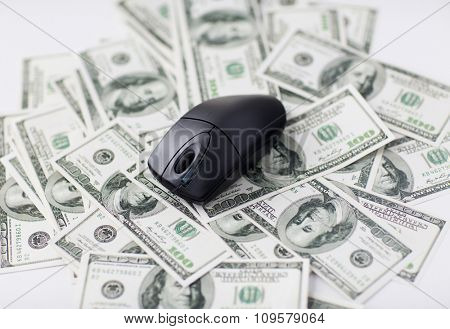 business, finance, internet earning and technology concept - close up of computer mouse and dollar cash money on table