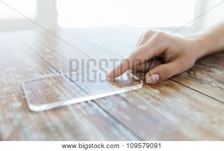 business, technology and people concept - close up of woman hand holding and showing transparent smartphone at home