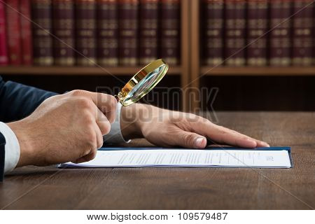 Lawyer Examining Documents With Magnifying Glass