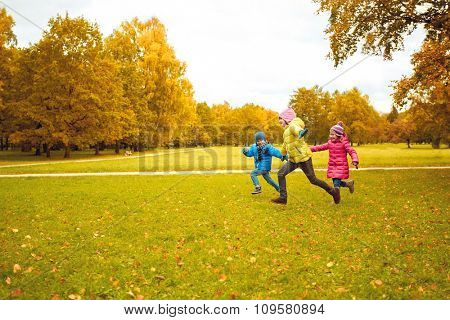 autumn, childhood, leisure and people concept - group of happy little kids playing tag game and running in park outdoors