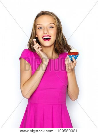 people, holidays, party, junk food and celebration concept - happy young woman or teen girl in pink dress with birthday cupcake