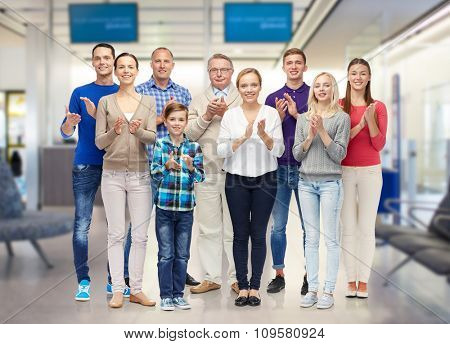 family, travel, tourism and people concept - group of smiling men, women and boy applauding over airport waiting room background