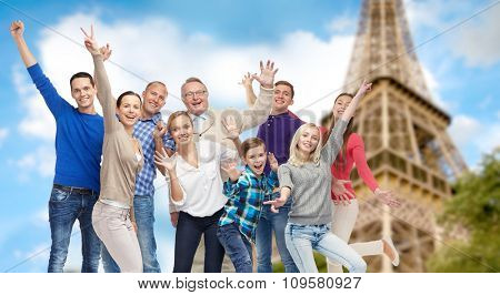 family, travel, tourism and people concept - group of happy men, women and boy having fun and waving hands over eiffel tower background