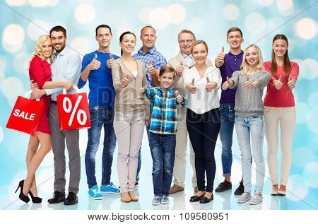 gesture, sale, discount, generation and people concept - group of happy people showing thumbs up and couple with shopping bags