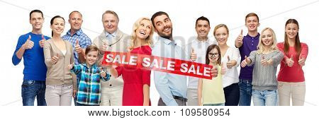 gesture, sale, shopping and people concept - group of smiling men, women and kids showing thumbs up and holding red sale sign or banner