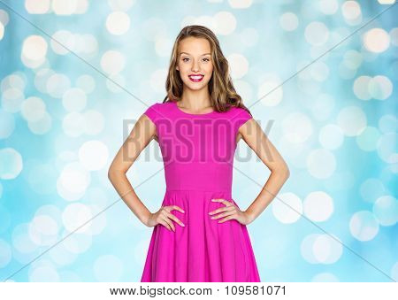 beauty, people, style, holidays and fashion concept - happy young woman or teen girl in pink dress over blue holidays lights background