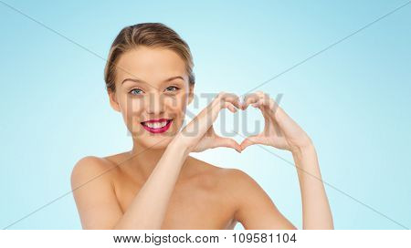 beauty, people, love, valentines day and make up concept - smiling young woman with pink lipstick on lips showing heart shape hand sign over blue background