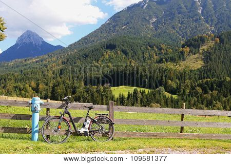 An Electric mountain bicycle parking near a blue Fire hydrant next to wooden fence with mountain background, Austria