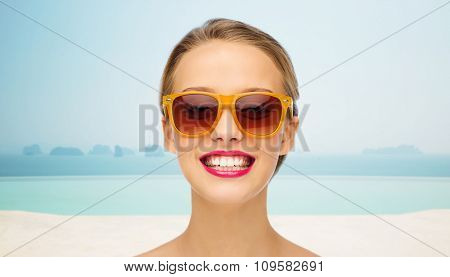 people, accessory, vacation, travel and fashion concept - smiling young woman in sunglasses with pink lipstick on lips over infinity edge pool background