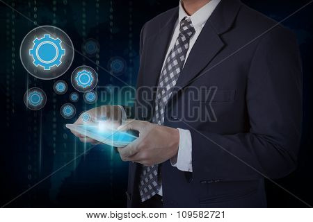 Businessman hand touch screen gear icons on a tablet.