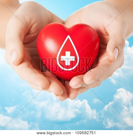healthcare, medicine and blood donation concept - female hands holding red heart with donor sign over blue sky and clouds background