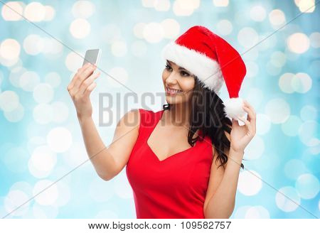 people, holidays, christmas and technology concept - beautiful sexy woman in red santa hat taking selfie picture by smartphone over blue lights background