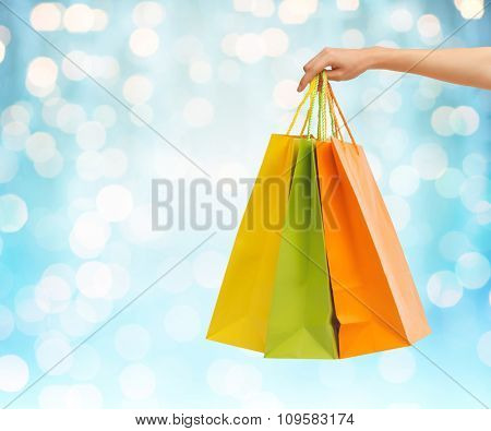 people, sale, consumerism and advertisement concept - close up of hand holding shopping bags over blue holidays lights background