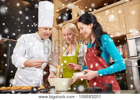 cooking class, culinary, bakery, food and people concept - happy group of women and male chef cook baking muffins in kitchen over snow effect