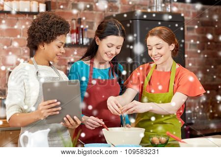 cooking class, friendship, food, technology and people concept - happy women with tablet pc in kitchen over snow effect