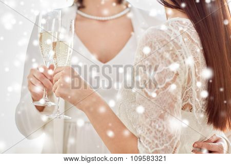 people, homosexuality, same-sex marriage, celebration and love concept - close up of happy married lesbian couple holding and clinking champagne glasses over snow effect