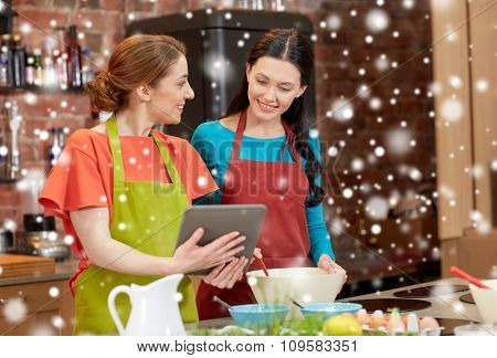 cooking class, friendship, food, technology and people concept - happy women with tablet pc computer in kitchen over snow effect