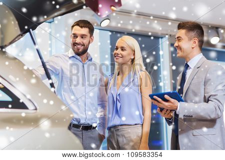 auto business, car sale, technology and people concept - happy couple with car dealer in auto show or salon over snow effect