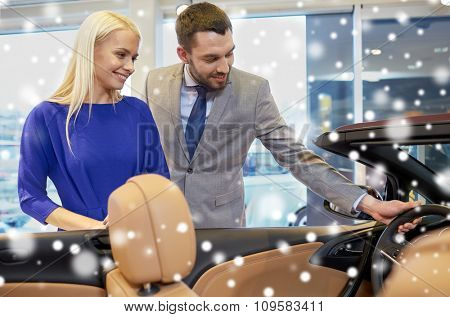 auto business, car sale, consumerism and people concept - happy couple buying car in auto show or salon over snow effect