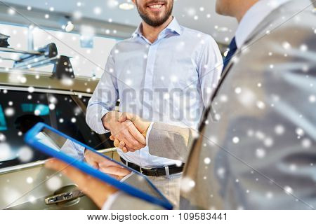 auto business, car sale, deal, gesture and people concept - close up of happy man and car dealer with tablet pc computer shaking hands in auto show or salon over snow effect