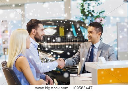 auto business, car sale, and people concept - happy couple with dealer shaking hands in auto show or salon over snow effect