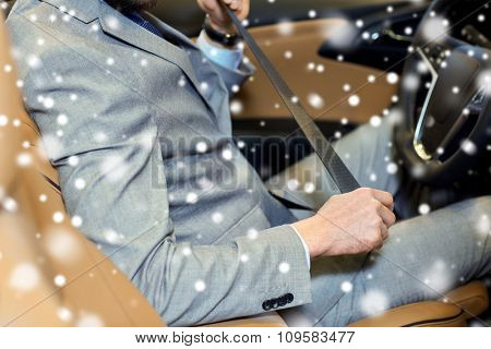 safety, driving and people concept - close up of man in elegant business suit fastening seat safety belt in car over snow effect