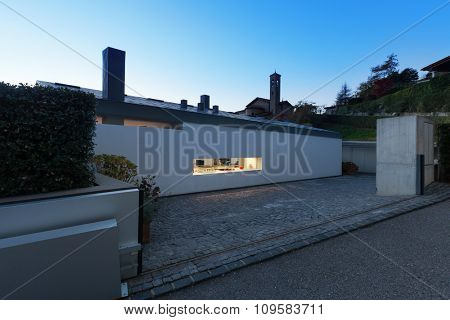 Modern house by night, illuminated window, external