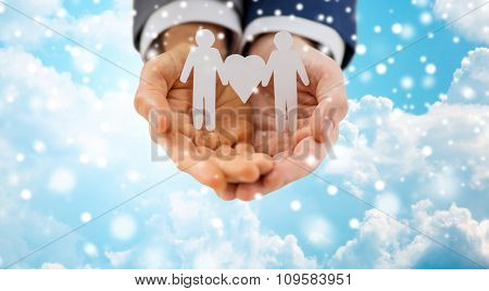 people, homosexuality, same-sex marriage and love concept - close up of happy male gay couple holding paper cutout love symbol over blue sky and clouds background over snow effect