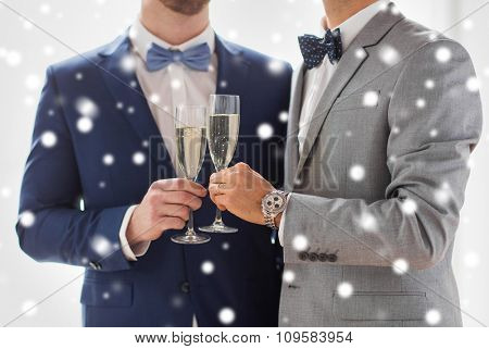 people, celebration, homosexuality, same-sex marriage and love concept - close up of happy married male gay couple in suits drinking sparkling wine and clinking glasses on wedding over snow effect