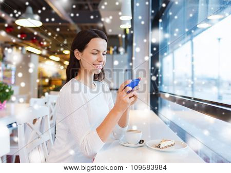 drinks, food, people, technology and lifestyle concept - smiling young woman with smartphone drinking coffee at cafe over snow effect