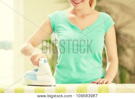 people, housework, laundry and housekeeping concept - close up of happy woman with iron and ironing board at home