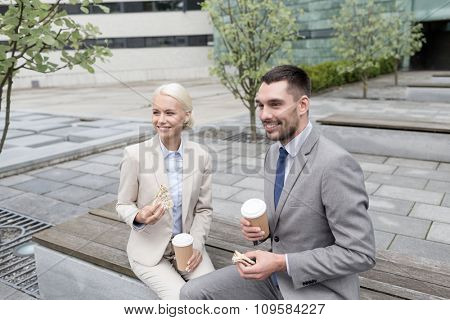 business, partnership, food, drinks and people concept - smiling businessmen with paper cups standing over office building