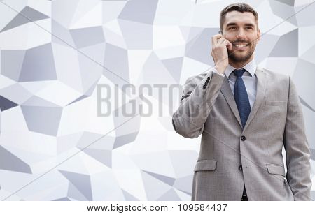 business, technology and people concept - smiling businessman with smartphone talking over office building over gray graphic low poly background