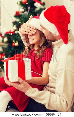 family, christmas, x-mas, happiness and people concept - smiling father surprise daughter with gift box covering eyes with hand